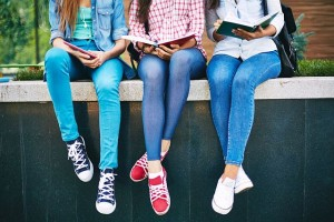 Modern teen girls reading outside